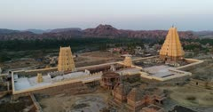 Drone footage of the UNESCO World Heritage temple complex area in Hampi, Karnataka, India, with the main temple Sri Virupaksha next to the Hampi village built along to the Tungabhadra river, granite boulders hill in the background, shot at sunset. The camera is going over the main temple towards the village and the river.