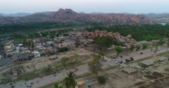 Drone footage of the UNESCO World Heritage temple complex area in Hampi, Karnataka, India, with the Hampi village and its main temple newly renovated Sri Virupaksha built along the Tungabhadra river, shot at sunset. The camera is going sideway along the village passing behind the biggest structure of the main temple.