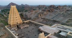 Drone footage of the UNESCO World Heritage temple complex area in Hampi, Karnataka, India, with the main temple newly renovated Sri Virupaksha and granite boulders hill with many temple ruins in the background, shot at sunset. The camera is turnng around the biggest structure of the main temple.