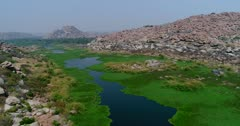 Drone footage of the countryside near Hampi, Karnataka, India, with the Tungabhadra river almost covered in green algae, various fields and granite like boulders forming hills along it, the Anjaneya hill with Hanuman temple is in the background. The camera is going over the river bed towards the monkey temple.