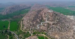 Drone footage of the countryside near Hampi, Karnataka, India, with the Anjaneya hill, Hanuman temple on top, the stairs to climb are painted in white and bright green rice fields are in the bottom. The camera is panning from the hill to the fields below.
