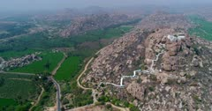 Drone footage of the countryside near Hampi, Karnataka, India, with the Anjaneya hill, Hanuman temple on top, the stairs to climb are painted in white and bright green rice fields are in the bottom. The camera is going sideway towards the hill.