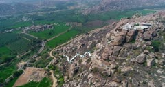 Drone footage of the countryside near Hampi, Karnataka, India, with the Anjaneya hill, Hanuman temple on top, the stairs to climb are painted in white and bright green rice fields are in the bottom. The camera is going sideway towards the hill while panning at the countryside.