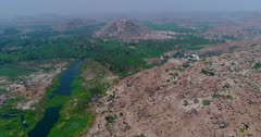 Drone footage of the countryside near Hampi, Karnataka, India, with the Tungabhadra river almost covered in green algae and granite like boulders forming hills along it, the Anjaneya hill with Hanuman temple is in the background. The camera is going over the river bed away from the monkey temple.