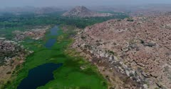Drone footage of the countryside near Hampi, Karnataka, India, with the Tungabhadra river almost covered in green algae and granite like boulders forming hills along it, the Anjaneya hill with Hanuman temple is in the background. The camera is going over the river bed away from the monkey temple while descending.