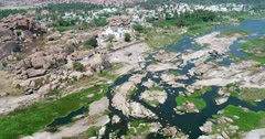 Drone footage of the countryside near Hampi, Karnataka, India, with the rocky bed of the Tungabhadra river, the granite like boulders forming hills along it, the Chinthamani Temple and the Anegundi village behind. The camera is going over the river turning around the temple.