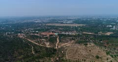 Drone footage of the countryside near Mysore, Karnataka, India, with its flat dry landscape scattered with trees, a huge golf area almost completely dry and the city and its palaces in the background. The camera is going over the countryside towards the city while ascending.