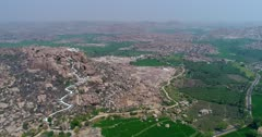 Drone footage of the countryside near Hampi, Karnataka, India, with rocky bouldery hills including the Anjaneya hill that has Hanuman temple on top of it, bright green rice fields between and the Tungabhadra river in the middle. The camera is doing a full 360 degrees panning of the area.