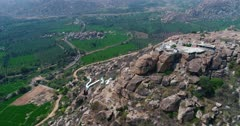 Drone footage of the countryside near Hampi, Karnataka, India, with the Anjaneya hill, Hanuman temple on top, the stairs to climb are painted in white and bright green rice fields are in the bottom. The camera is going towards the hill while tilting down at the stairs.