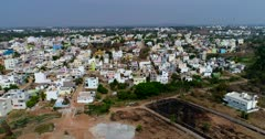 Drone footage of Alanahalli village near Mysore, Karnataka, India, with the colorful square buildings of its residential area. The camera is going towards the buildings.