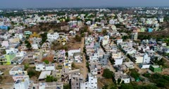 Drone footage of Alanahalli village near Mysore, Karnataka, India, with the colorful square buildings of its residential area. The camera is going sideway along the buildings.