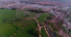 Drone footage of countryside near Mysore, Karnataka, India, with bright green rice fields at various stage growing along the Kaveri river, its other side pretty dry with red earth. The camera is facing down at the fields and is panning along them whle tilting up.