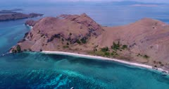 Drone footage of Komodo National Park, Indonesia with a beach of Sebayur kecil island and the shallow colorful coral reef in front, a diving boat is anchored nearby. The camera is facing down at the beach and is going sideway while descending.