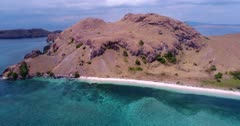 Drone footage of Komodo National Park, Indonesia with a beach of Sebayur kecil island and the shallow colorful coral reef in front, a diving boat is anchored nearby. The camera is facing the beach and is going backward over the water while descending.