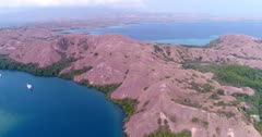 Drone footage of Komodo National Park, Indonesia with Rinca island near the ranger park, mangroves are growing along the shore and diving boat are anchored in a bay. The camera is going along the shore while panning towards the ranger park area.