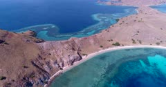Drone footage of Komodo National Park, Indonesia with Gili Lawalaut, its dry rocky land with sandy bay and its turquoise water with pristine coral reef on all sides, a diving boat is anchored in a bay. The camera is going backward over the water while ascending and panning along the island.