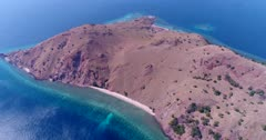 Drone footage of Komodo National Park, Indonesia with Gili Lawalaut, its dry rocky land with sandy bay and its turquoise water with pristine coral reef on all sides, diving boats are anchored in a bay. The camera is panning the island from side to side.
