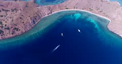 Drone footage of Komodo National Park, Indonesia with Gili Lawalaut, its dry rocky land with sandy bay and its turquoise water with pristine coral reef on all sides, diving boats are anchored in a bay. The camera is facing down at the water and is going towards the island over the boats.