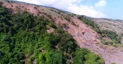 Drone footage of Sangeang island, Indonesia with its volcanic ground scattered with small trees and bushes, an area is covered by plant. The camera is going backward along the coast.
