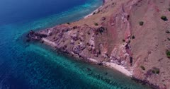 Drone footage of Komodo National Park, Indonesia with Gili Lawalaut, its turquoise water over pristine coral reef, rocky landscape scattered with small trees. The camera is facing down at the island and is going along it while panning.