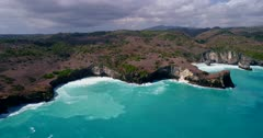 Drone footage of the west coast of Nusa Penida, Indonesia near Angel Billabong and broken beach with its rocky shore scattered with few bushes, big waves are crashing into the rocks. The camera is facing the coast and is going towards it.