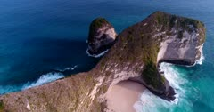 Drone footage of Kelingking Beach on the west coast of Nusa Penida, Indonesia with its secluded white sand beach surrounded by crystal blue water at the bottom of steep rocky cliff. The camera is facing the headland and is turning around it panning towards the beach.