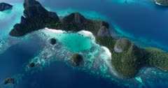 Drone footage of Raja Ampat, Indonesia with the hilly islands covered in tropical vegetation, white sand beaches and colorful shallow coral reefs in the west of Wayag or Wajag island. The camera is facing down at the beaches and is ascending while turning.
