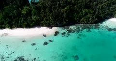 Drone footage of Raja Ampat, Indonesia with 2 zodiacs on secluded white sand beach surrounded by tropical vegetation and colorful pristine coral reef in the west of Wayag or Wajag island. The camera is facing down at the boats and is turning around them.