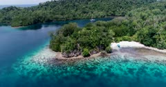 Drone footage of Raja Ampat, Indonesia with a small sailing boat anchored in a bay off Janggelo or Yanggelo island, turquoise water and shallow coral reef around. The camera is facing the coast and is going sideway along it while panning.