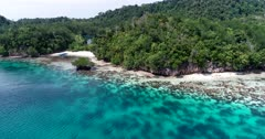 Drone footage of Raja Ampat, Indonesia with a small sailing boat anchored in a bay off Janggelo or Yanggelo island, turquoise water and shallow coral reef around. The camera is facing the coast and is going towards it before tilting down at the boat.