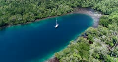 Drone footage of Raja Ampat, Indonesia with a small sailing boat anchored in a bay off Janggelo or Yanggelo island, turquoise water and shallow coral reef around. The camera is facing down at the boat and is going backward along the bay.