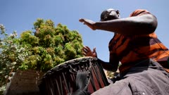 Footage of man playing djembe from the side, shot at 50fps at knee level looking up.