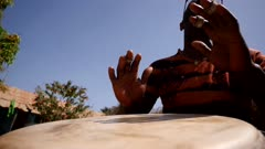 Footage of man playing djembe from the front with the focus on the hands hitting the drumhead, shot at 50fps at knee level looking up.