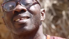 Footage of black man face smiling and moving with the music while playing djembe, shot at 50fps at knee level.