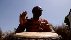 Footage of man playing djembe from the font, shot at 50fps at knee level looking up and slowly zooming in.