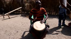 Footage of man playing djembe from the front, shot at 50fps.