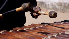 Footage of black man playing Balafon instrument standing, shot at 50fps from 3/4 angle.