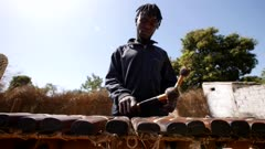 Footage of black man playing Balafon instrument standing, shot at 50fps from the front at instrument height.