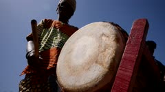 Footage of black man in traditional clothes playing dundun or dunun drum, shot at 50fps from 3/4 angle at knee height looking up.