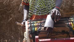 Footage of black man in traditional clothes playing dundun or dunun drum and kenken which consists of hitting a metallic ring on steel bell fixed on top, shot at 50fps from the front at instrument height.