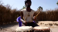 Footage of black man playing dundun or dunun drum in vertical position with two wooden sticks while sitting, shot at 50fps from the front at instrument height.
