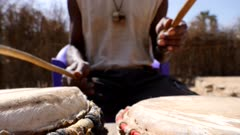 Footage of black man playing dundun or dunun drum in vertical position with two wooden sticks while sitting, focus on skin of dundun or dunun, shot at 50fps from the front at instrument height.