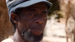 Footage of black man head with hat playing dundun or dunun drum in vertical position with two wooden sticks while sitting, shot at 50fps from 3/4 angle at head height.
