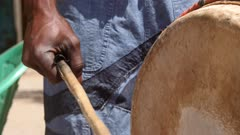 Footage of black man hand holding wooden stick and hitting the skin of dundun or dunun drum, shot at 50fps from 3/4 angle at instrument height.