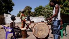 Footage of black men playing different african instruments like dundun or dunun drum, kenken, balafon and djembe, shot at 50fps at instrument height.
