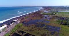 Aerial footage of coast of island with black sand beach and green rice paddies next to, colorful shallow water in front and waves crashing. The camera is ascending along the coast while tilting down.