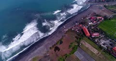 Aerial footage of coast of island with black sand beach and green rice paddies next to, colorful shallow water in front and waves crashing. The camera is ascending along the coast while panning and tilting up.