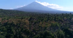 Aerial footage of the Agung volcano with its side covered in lush tropical vegetation and hill at the bottom. The camera is ascending sideway along the hill.