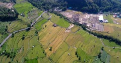 Aerial footage of rice paddies at various stages from just harvested to bright green ones at the bottom of hills covered in tropical forest, road passing nearby. The camera is going over the fields while panning.