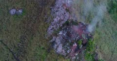 Aerial footage of the Batur volcano with smoke coming out of its rocky ground. The camera is panning around the smoke.